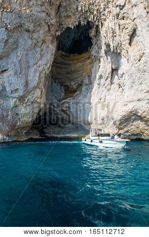 Capri Italy - October 20 2008: A boat with tourists leaving the Arco Naturale sea cave on the south coast
