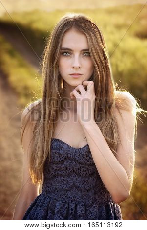 portrait of a beautiful young girl goes on a flower meadow at sunset