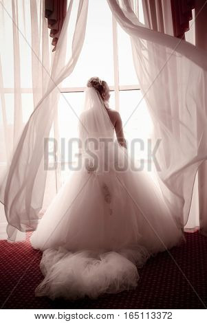 beautiful young bride standing beside a large window waiting for a groom