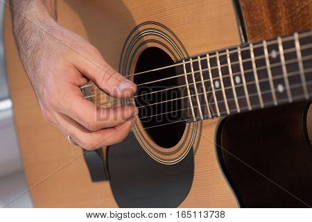 Man's hand playing acoustic guitar. close up
