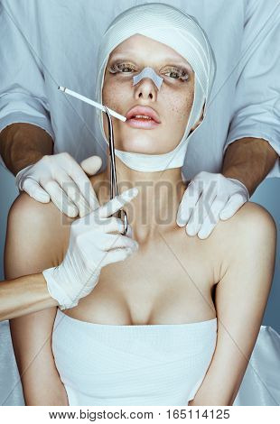 Young attractive woman looks sad and indifferently smoking cigarette. Photo of woman wrapped in medical bandages after plastic surgery.