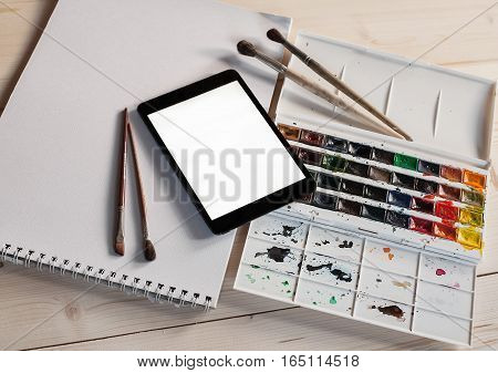 Tablet PC with watercolor paints and brushes on wooden table. Idea of technology involvement into art. Modern concept of painting