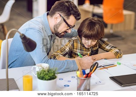 I want to help. Handsome man holding pencil in his right hand showing to his son how to do that task
