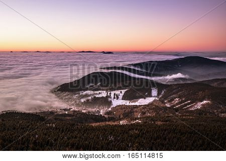 Colored sky with inversion in the valley below Jestedem in northern Bohemia. Aerial view from the top of Jested. Czech Republic