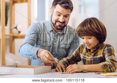 Attractive smiling boy wearing checked shirt sitting at the table making picture with his father