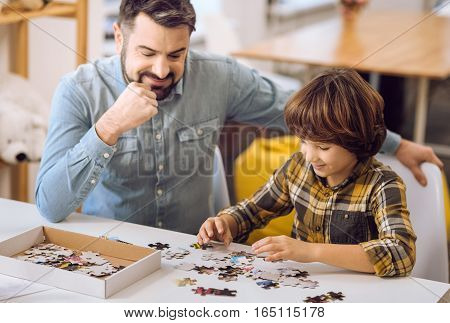 Happy father wearing jeans shirt keeping his hand on the chic while looking at his playing son