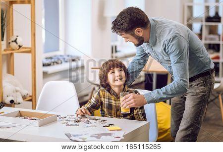 Provident man wearing jeans shirt looking at boy while giving him orange juice