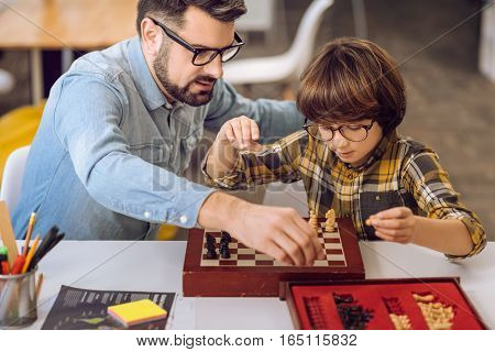 It is our day. Smart boy wearing spectacles holding pawn in his left hand while playing chess with his father