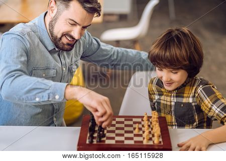 My turn. Handsome man wearing jeans shirt holding pawn in his hand while thinking of right move