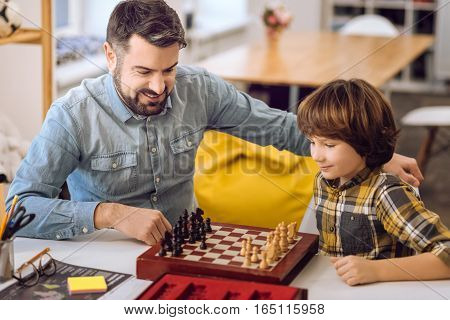 Our hobby. Attractive boy wearing checked shirt holding pawn in his left hand while thinking about move