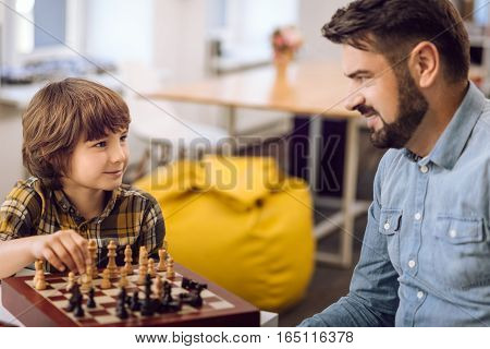 Believe you. Smiling boy wearing checked shirt holding pawn in his hand while looking at his father