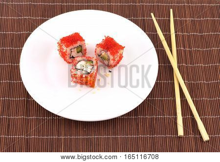 Three sushi pieces on white plate and two chopsticks over brown wicker straw mat closeup