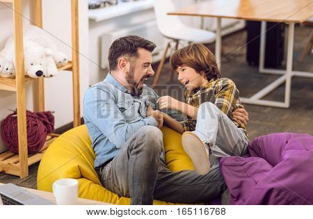 Love you son. Positive delighted man wearing jeans and shirt looking at his little son while sitting on poufs