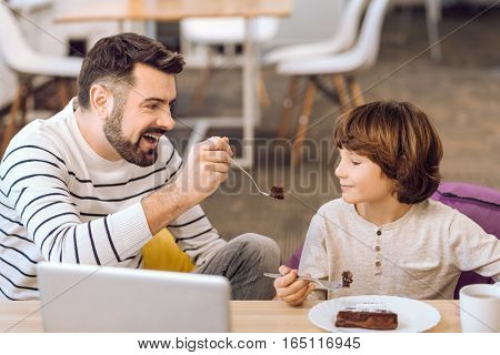 Love sweets. Positive delighted bearded man wearing stripped sweater looking at his son while feeding him