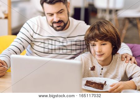 Happy Sunday. Handsome boy using laptop for watching videos eating chocolate cake while sitting near his father