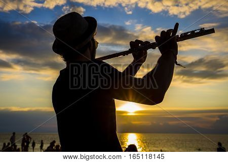 KOH PHANGAN THAILAND - JANUARY 14 2017: An unidentified man play the flute at sunset on the beach during a full moon party in island Koh Phangan Thailand