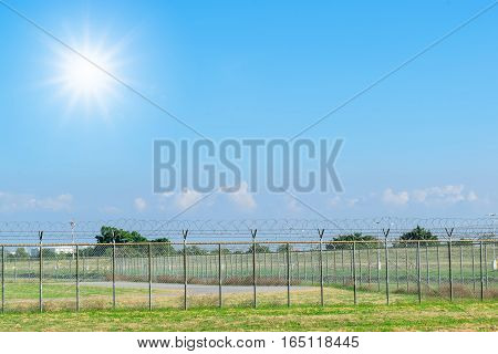 Closeup barbed wire fence for boundary on the grass with colorful sky.