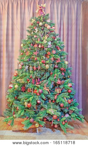Green Christmas Tree With Many Vibrant Colored Ornaments, Colored Lights, Decorated, Close Up, Indoo