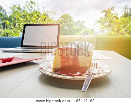 A Piece Of Cake And Laptop On Wooden Table In The Morning