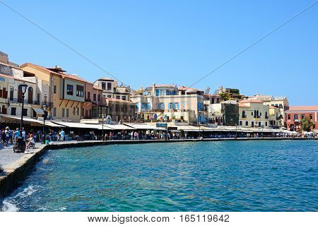 CHANIA, CRETE - SEPTEMBER 16, 2016 - Tourists walking along the restaurant lined quayside in the inner harbour Chania Crete Greece Europe, September 16, 2016.