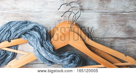 Wooden clothes hangers on bright background. What nothing to wear concept. Woman clothing banner