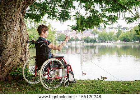 Senior woman in wheelchair, enjoying time outdoors.