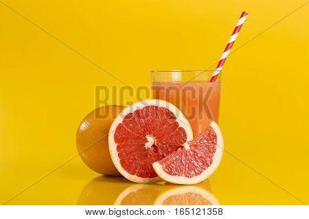 Whole red grapefruit cross section and a slice placed next to a glass of grapefruit juice with drinking straw isolated on orange background. Focus stacked image