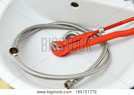 plumbing wrench and faucet pipe in white sink