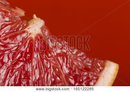 Detail of a red grapefruit slice isolated on red background. Selective focus