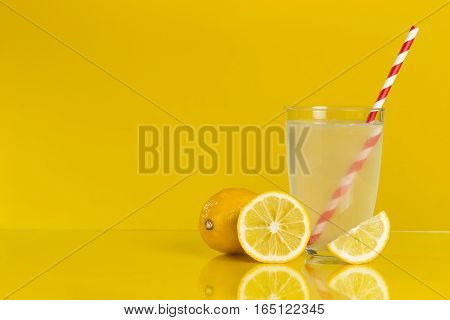 Studio shot of a glass of lemonade with a striped red and white drinking straw and a whole cross section and a slice of lemon fruit placed next to it. Focus stacked image