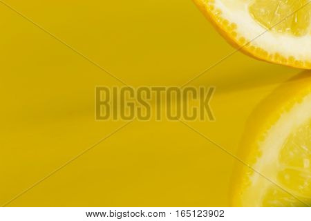 Detail of a lemon slice isolated on yellow background studio shot