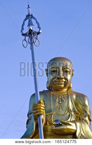 Gold Buddha Statue on blue sky background