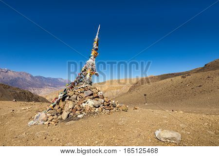 Traditional Tibetan pile of stones and colored flags on the pass, Himalayas, Nepal