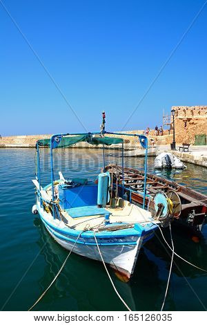 CHANIA, CRETE - SEPTEMBER 16, 2016 - Traditional fishing boat in the harbour with the harbour wall to the rear Chania Crete Greece Europe, September 16, 2016.