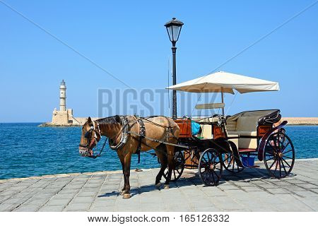 Horse drawn carriage on the quayside with the Venetian lighthouse at the harbour entrance to the rear Chania Crete Greece Europe.
