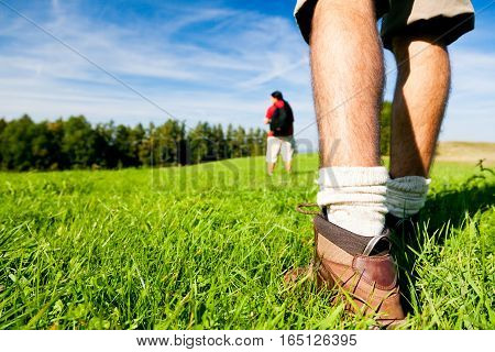 young couple hiking outdoors in summer, focus on feet.