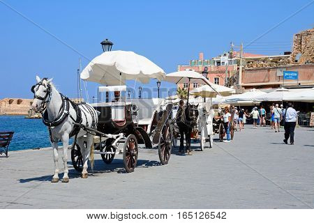 CHANIA, CRETE - SEPTEMBER 16, 2016 - Horse drawn carriages on the quayside Chania Crete Greece Europe, September 16, 2016.