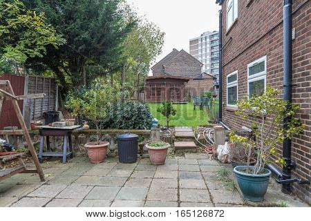 Patio, back garden and wooden cabin at the end.