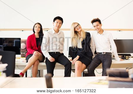 a young creative team is posing for a group shot in their office. they've just started their new business and they will surely do well.