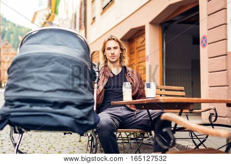 Young father with baby stroller having coffee at a cafe in Heidelberg, Germany.