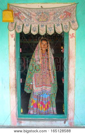 GUJARAT, INDIA - DECEMBER 20, 2013: Tribal woman at the entrance of her house (Bhunga) in a local village near Bhuj
