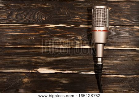 Grey microphone on wooden background. Place for text