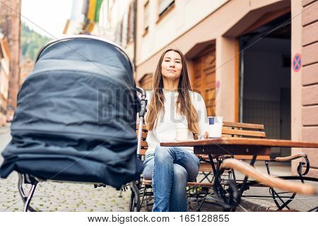 Young mother with baby stroller having coffee at a cafe in Heidelberg, Germany.