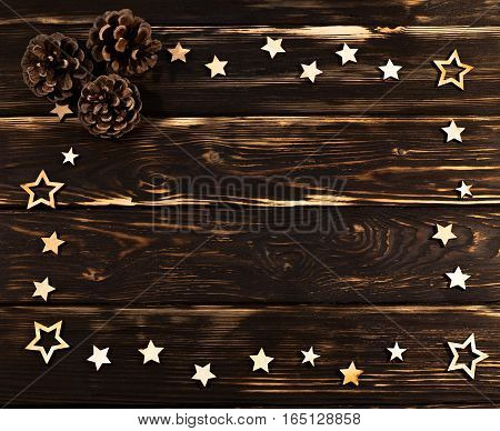 Wooden background with christmas wooden stars folded on the perimeter and cones. Place for text