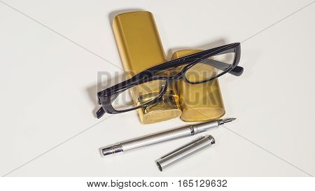 Black glasses, gold case and a pen. Isolate white background.