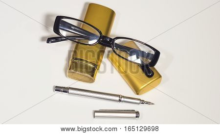 The glasses, gold case and a pen. Isolate white background.