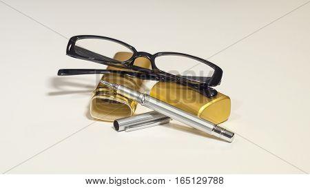 An elegant black glasses, case, metal pen on the white isolate background.
