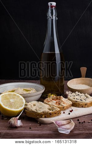 The homemade hummus and ingredients in rustic style.