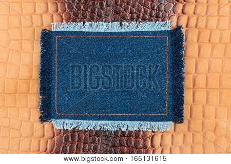 Frame made of denim with a fringe is on the brown crocodile skin with space for your text