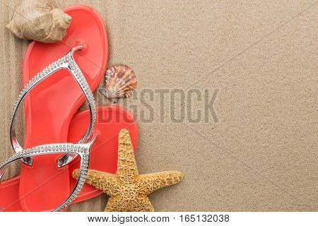 Red flip-flops with rhinestones and seashell starfish on the sand. With place for your text